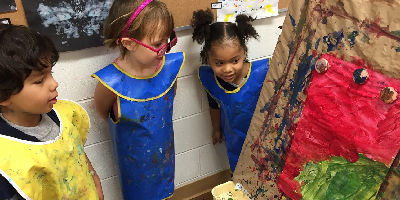Three PIC preschoolers admiring art on an easel